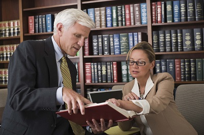 Two lawyers reading insurance claim